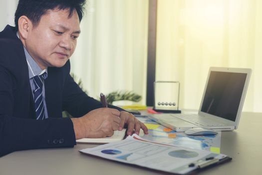 Picture of a serious young businessman with information placed on a desk to make business investment decisions.
