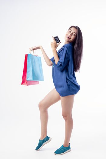 Portrait of a beautiful woman in her hand Carrying a credit card and a colorful shopping bag, isolated on white background