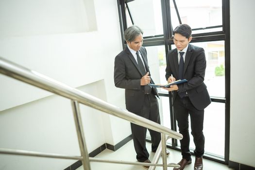 Two executives are talking to each other using a digital tablet standing in the office corridor, colleagues talk about apps for managing business in the office.