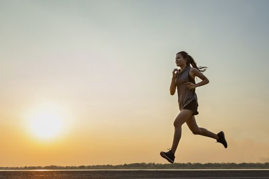 The silhouette of young women running and exercising at sunset with the sun in the background, colorful sunset sky