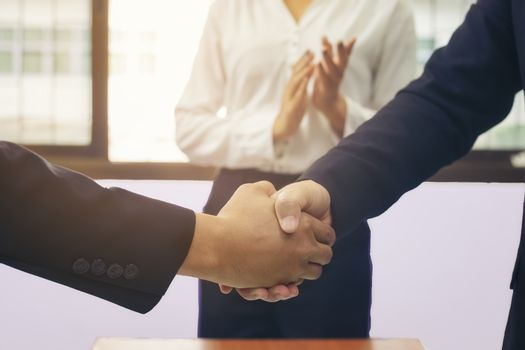 Business people shaking hands at meeting while theirs colleagues clapping and applauding. Success teamwork, partnership and handshake