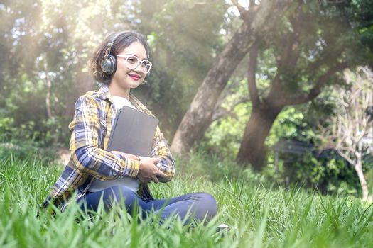 Beautiful woman listened to music while sitting happily on the lawn in the park.