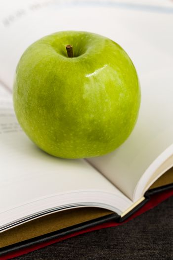 Green apple with book illustrated knowledge and wisdom concept.