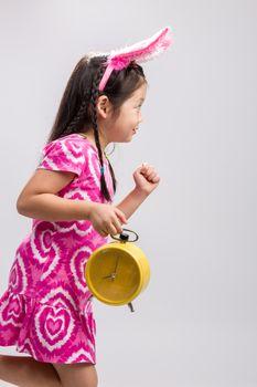 Child holding clock illustrating time concept on white background.