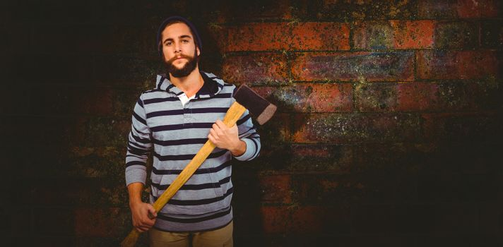 Portrait of confident hipster with hooded shirt holding axe against texture of bricks wall