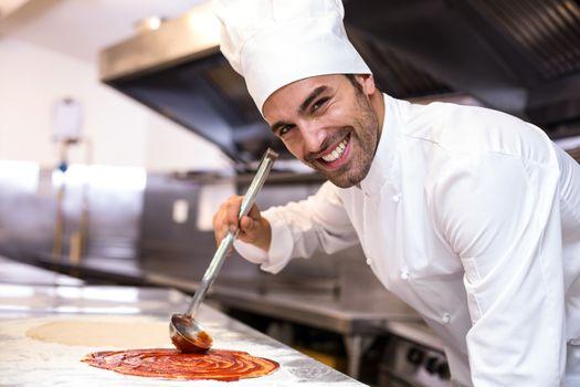 Pizza chef put sauce on base