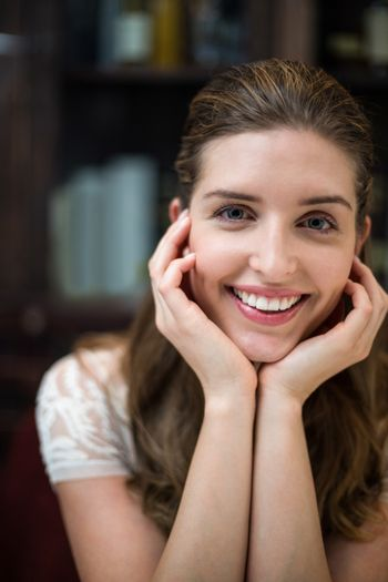 Smiling woman at restaurant with hands on chin