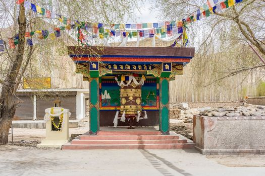 Colorful traditional tibetan prayer wheel of village in Leh, Ladakh. The prayer bell is spun for good luck and can be seen everywhere in Ladakh. The mantra written on the bell is sacred