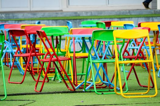 Multi-color steel chair set on green plastic grass In the playgr