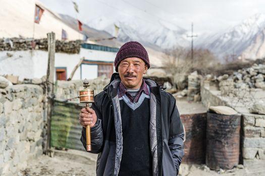 Old man swings hand prayer wheel in Leh, Ladakh, Jammu and Kashmir, India