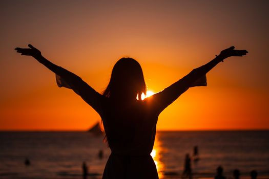 Silhouette of woman raising arms to golden sunset over sea. Freedom, success and hope concept. Girl relaxing and enjoying peace and serenity on beautiful nature, vacation concept.