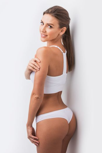 Young beautiful woman in white cotton underwear touching own skin standing , white background