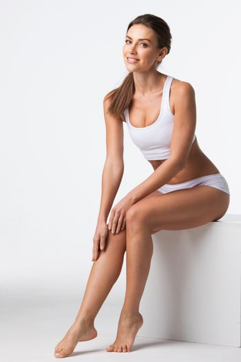 Young beautiful woman in cotton underwear sitting and touching own legs skin, white background