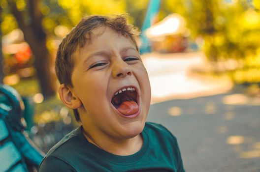close portrait of a laughing young boy in the forest