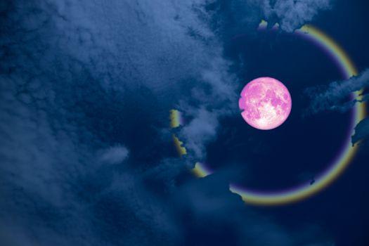 full pink halo moon and rainbow on night sky