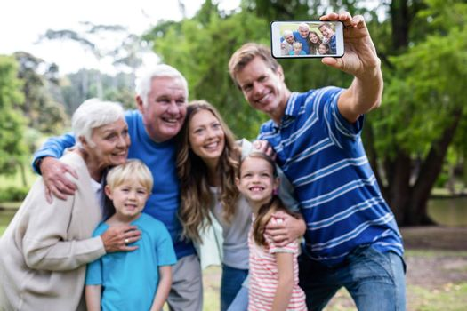 Multi-generation family taking a selfie in the park on a sunny day