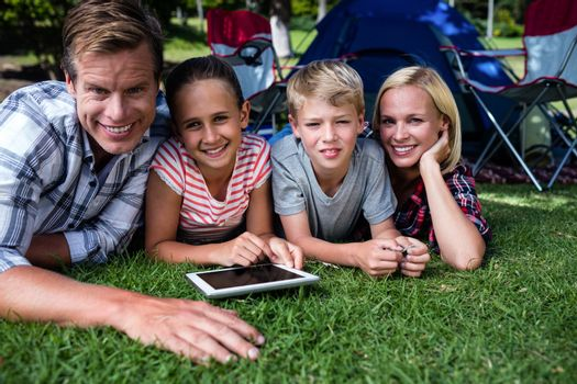 Portrait of a family lying on grass and using digital tablet at campsite