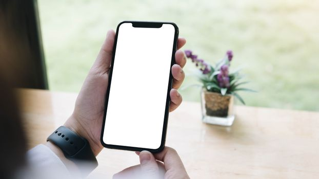Cropped shot top view of woman hands using smartphone mockup at