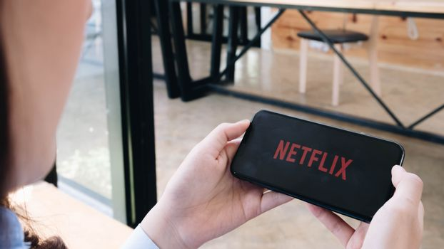 CHIANG MAI, THAILAND, JUN 7 , 2020: Young woman in a hammock opening Netflix in her smartphone. Millennial girl resting with her cell phone in her hands and the Netflix logo in the screen.