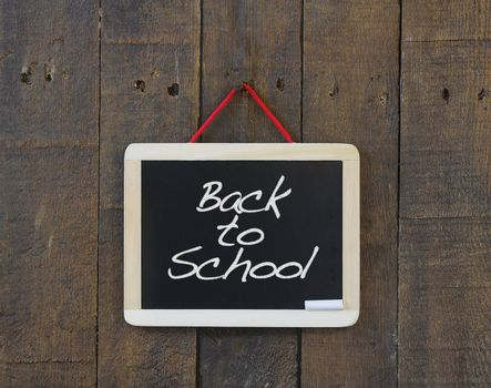 Blackboard hanging on a old wooden wall with Back to school.