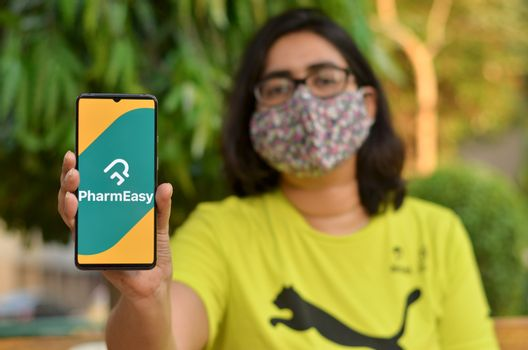 New Delhi, India, 2020. Girl wearing mask with Pharmeasy app on the mobile phone. Only essential services / products are allowed to be delivered during Corona Virus (Covid-19) lockdown