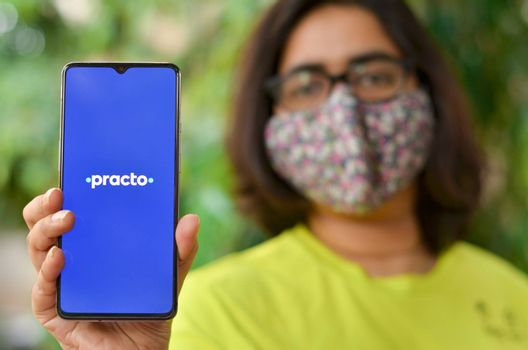 New Delhi, India, 2020. Girl wearing mask with Practo app on the mobile phone. Only essential services / products are allowed to be delivered during Corona Virus (Covid-19) lockdown