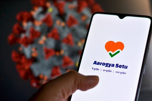 New Delhi, India, 2020. Aarogya Setu app, developed by government of India to track the Covid-19 status, Logged in on a mobile infront of a screen showing microscopic 3D illustration of Corona Virus