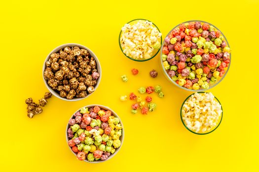 Flavored popcorn on yellow table from above