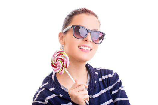 Beautiful young girl in casual clothes with sunglasses holding a colorful lollipop, isolated on white background.
