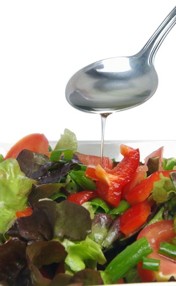 spoon with oil over fresh salad