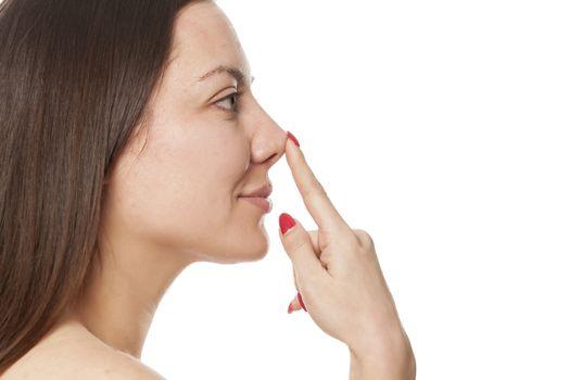 woman touching jer nose