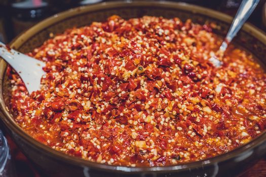 Big bowl of freshly chopped chillies and garlic in a spice shop on street market in Yangshuo town, China