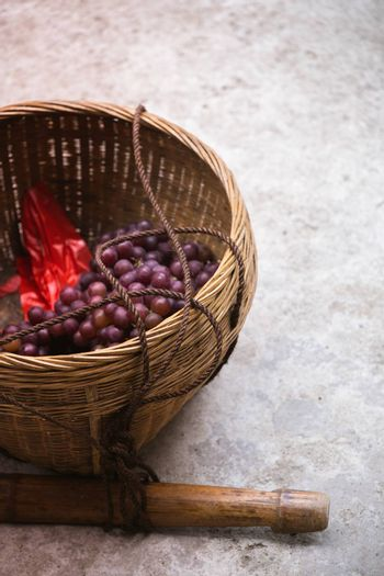 A vertical shot of fresh grapes in a basket on the ground