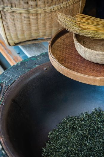 Vertical shot of woven baskets, broom and dried tea leaves in a huge bowl