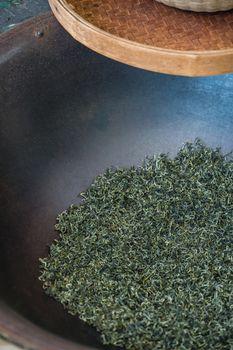 Vertical shot of dried tea leaves in a huge black bowl