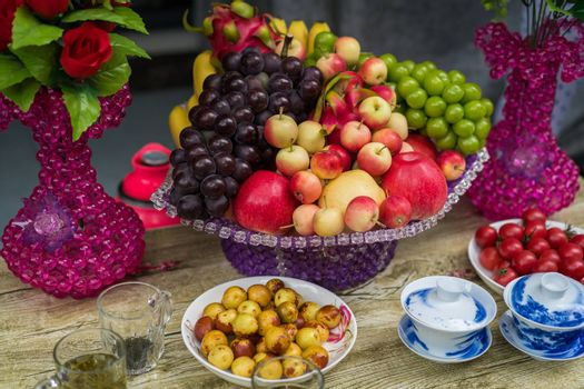 Decorative glass porcelain basket with ripe fresh grapes, apples and dragonfruit on a table in a chinese tea shop