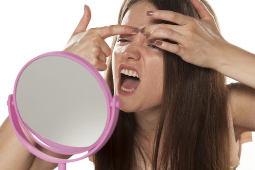 woman squeezing her pimples