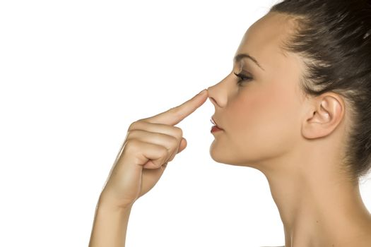 woman touches her nose with her finger