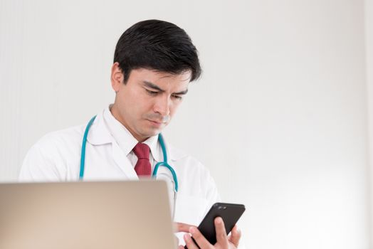 A doctor woman has to work with a mobile phone at the hospital.
