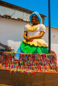 Brazilian woman of African descent, smiling, dressed in traditional Baiana attire in Pelourinho, Salvador, Bahia, Brazil.