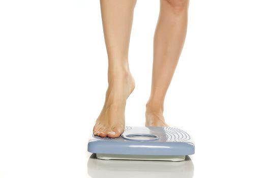 Pretty female legs on scales