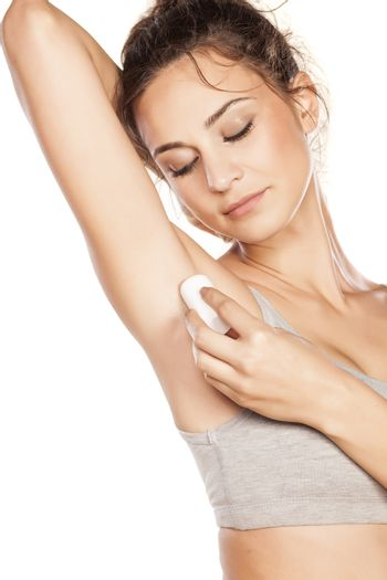 beautiful girl applied deodorant stick to the armpits