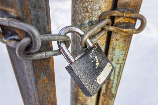 Closed padlock and chains hanging on old and rusty iron gates
