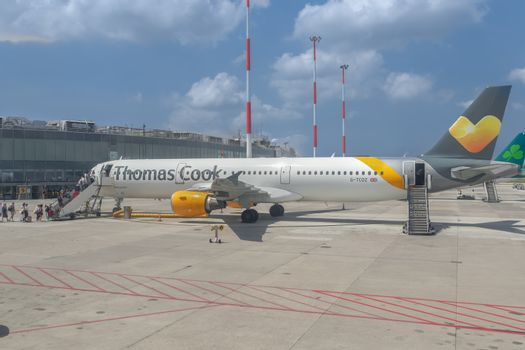 Naples, Italy Thomas Cook Airbus A 321 taxied on airport runway tarmac with boarding passengers and logo on wing.