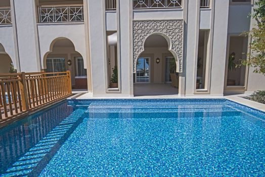 Luxury tropical hotel resort room terrace by private outdoor swimming pool
