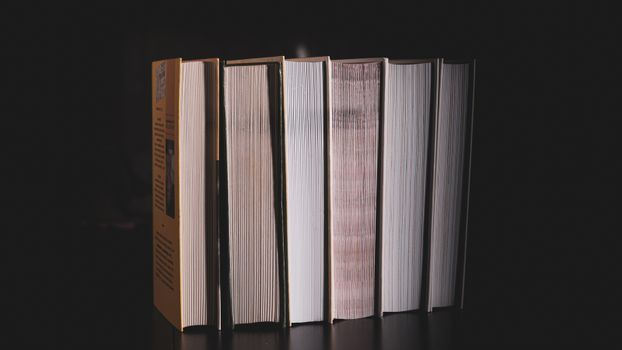 High messy stack of books on a black background with space for text message.