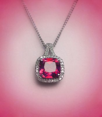 red diamond necklace on pink surface