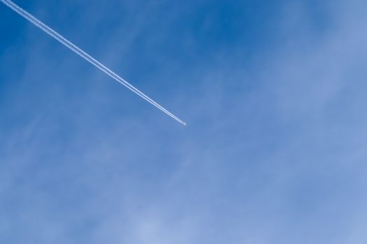 Aircraft condensation contrails in the blue sky inbetween some c