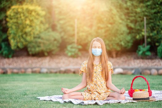 Beautiful little girl meditates in a yoga pose on a picnic in the the park. Girl wearing a protective mask outdoors because of the coronavirus pandemic.