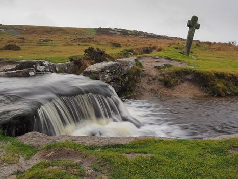 Windy Post granite cross standing behind a waterfall cascading over rocks on the Grimsbridge and Sortridge leat under a grey sky, Dartmoor National Park, Devon, UK